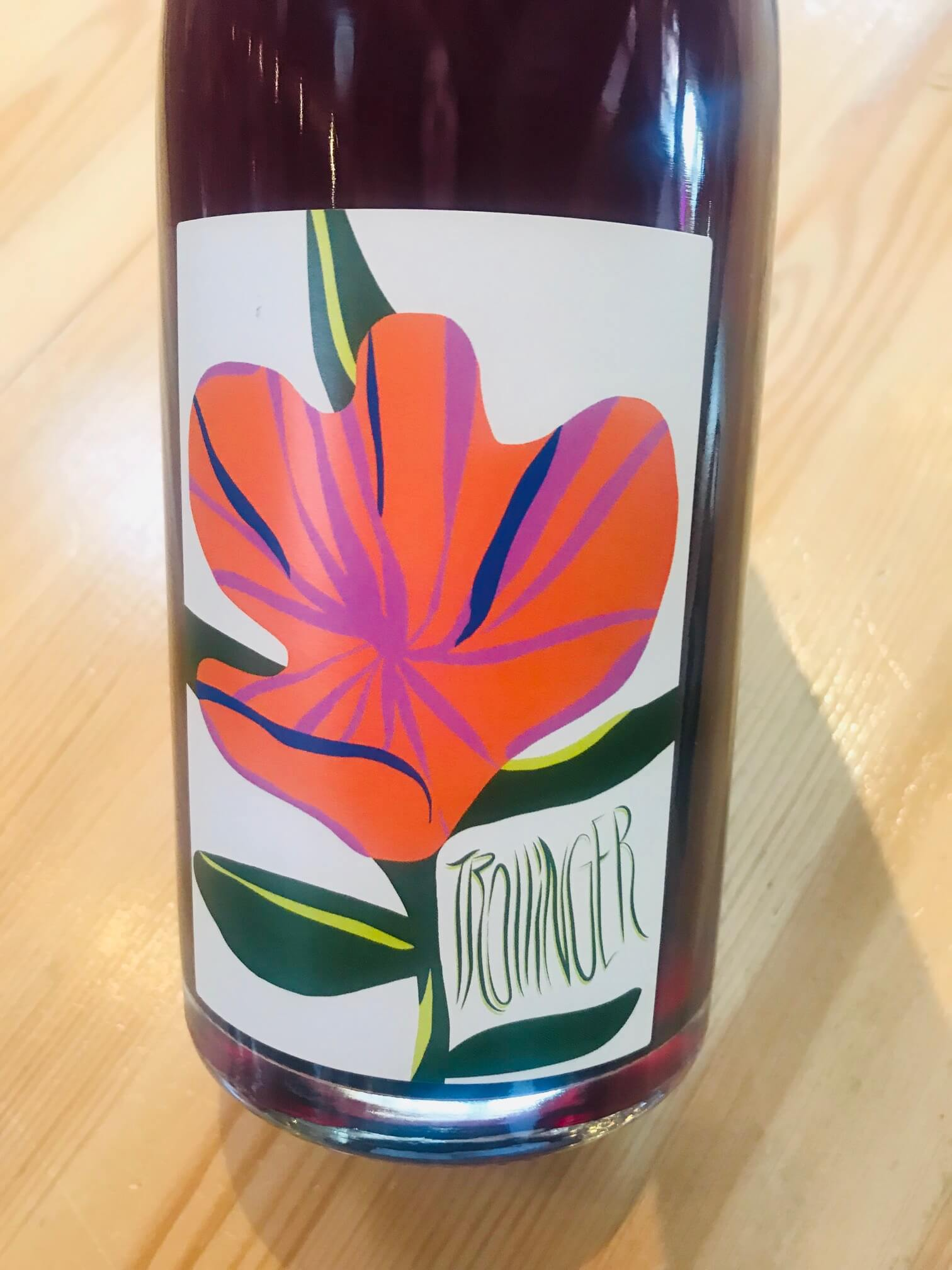 Bottle of Trollinger red wine with a cartoonish artsy red flower on the label